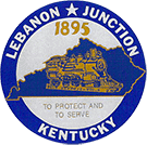 City Seal: Goldenrod yellow steam engine sits inside the outline of the state of KY with '1895' above it and 'To Protect and To Serve' below it, all surrounded by a blue circle with 'Lebanon Junction Kentucky' written along the outside